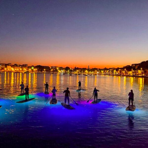 night paddleboarding with view of split