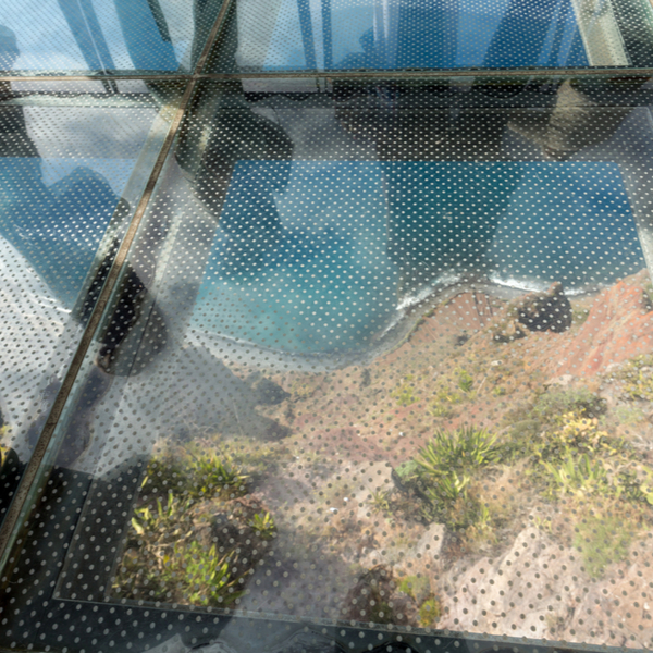 glass skywalk with view over cliffs and ocean in madeira