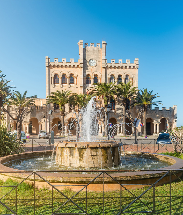 Fountain in a park with town hall building in background in Ciutadella on sunny summer day, Menorca island, Spain