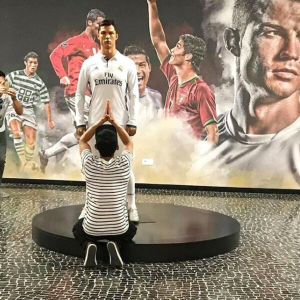 person posing with ronaldo statue at madeira museum