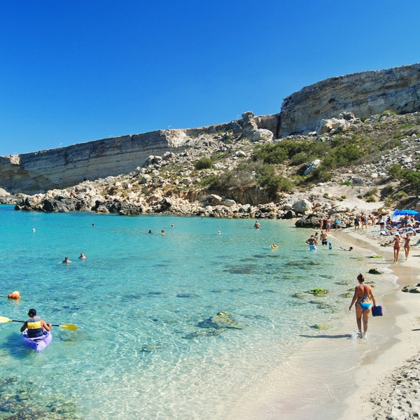 people swimming in sea at malta's paradise bay
