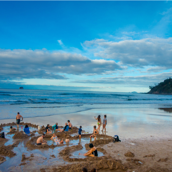people digging personal hot springs at Hot Water Beach in Auckland