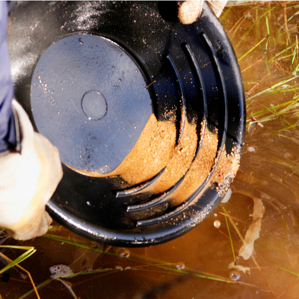person gold panning in lapland river
