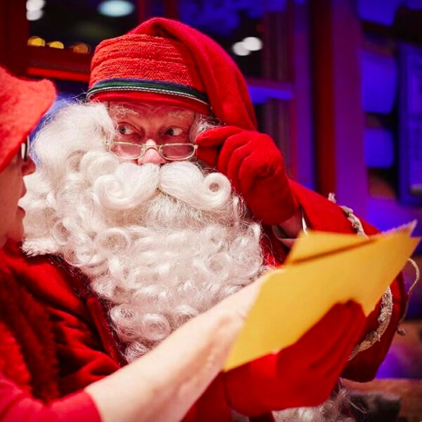 santa claus reading letters at his post office in lapland